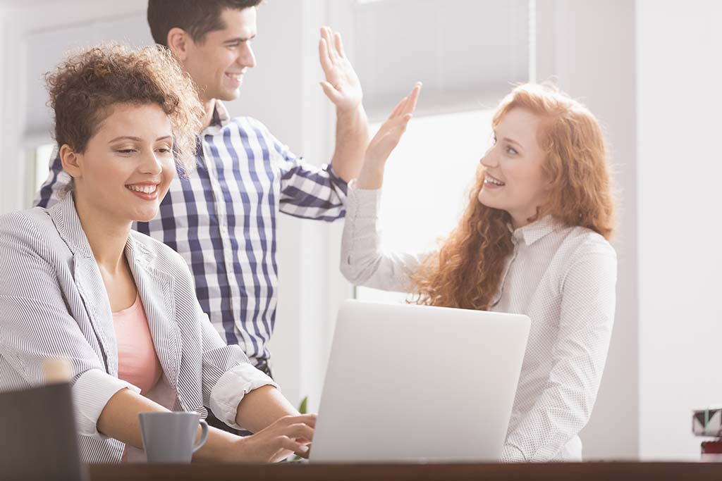 IT specialist high fiving team members